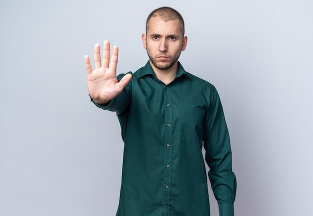 停止ジェスチャーを示す緑のシャツを着ている厳格な若いハンサムな男