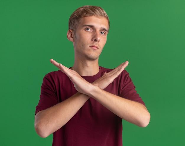 緑の壁に孤立していないジェスチャーを示す赤いシャツを着ている厳格な若いハンサムな男