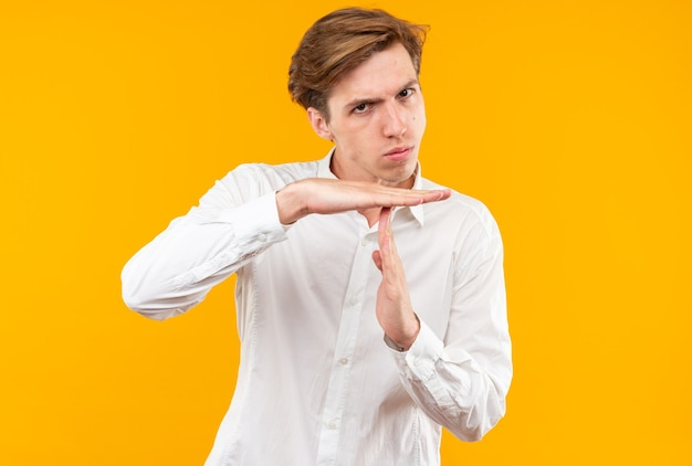 Rigoroso giovane bel ragazzo che indossa una camicia bianca che mostra il gesto di timeout isolato sul muro arancione