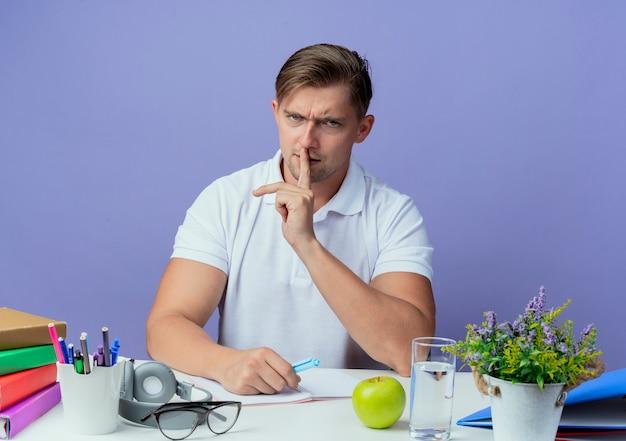침묵 제스처를 보여주는 학교 도구로 책상에 앉아 엄격한 젊은 잘 생긴 남자 학생