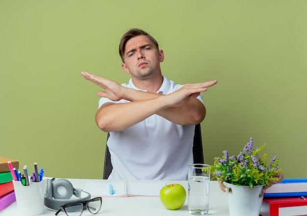 Rigoroso giovane studente maschio bello seduto alla scrivania con strumenti scolastici che mostra il gesto di non isolato su verde oliva