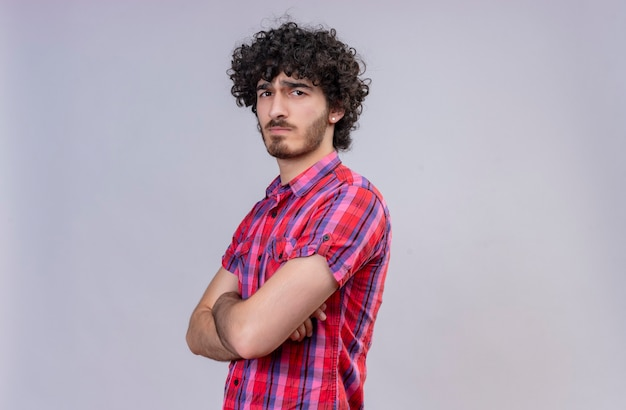 A strict young handsome man with curly hair in checked shirt holding hands folded