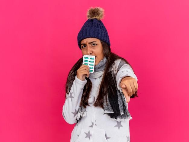 ピンクで隔離されたジェスチャーを示す口の周りに丸薬を保持しているスカーフと冬の帽子をかぶっている厳格な若い病気の女の子