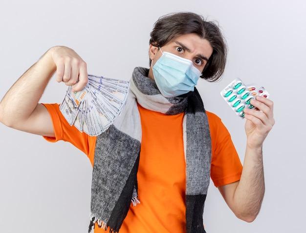 白い背景で隔離の丸薬と現金を保持しているスカーフと医療マスクを身に着けている厳格な若い病気の男 無料写真