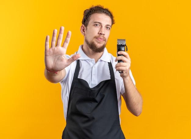 黄色の背景で隔離の停止ジェスチャーを示すバリカンを保持している制服を着ている厳格な若い男性理髪師