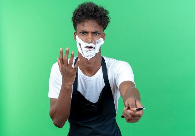 Barbiere maschio giovane rigoroso che indossa uniforme con crema da barba