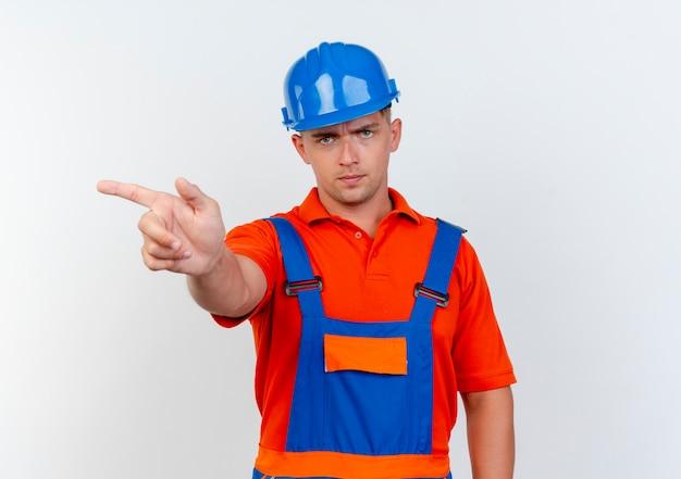 白の側に制服と安全ヘルメットポイントを身に着けている厳格な若い男性ビルダー