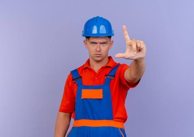 紫色のジェスチャーを示す制服と安全ヘルメットを身に着けている厳格な若い男性ビルダー