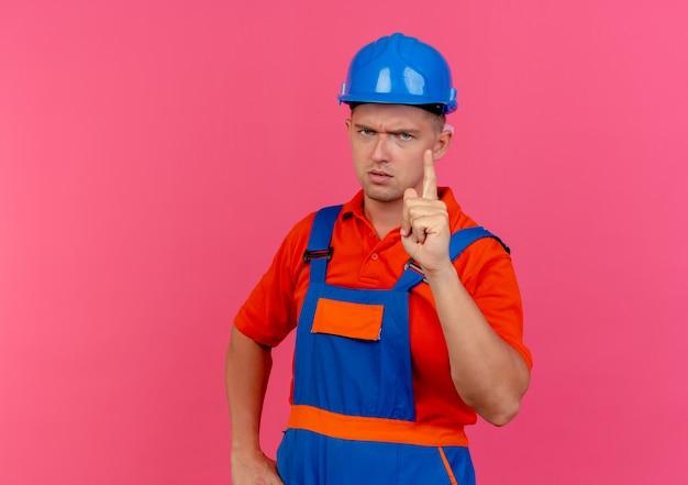 ピンクの1つを示す制服と安全ヘルメットを身に着けている厳格な若い男性ビルダー