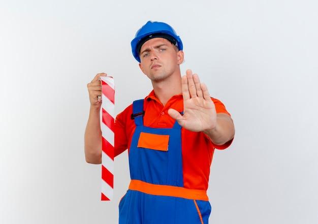 Rigoroso giovane costruttore maschio che indossa l'uniforme e casco di sicurezza tenendo il nastro adesivo e mostrando il gesto di arresto su bianco