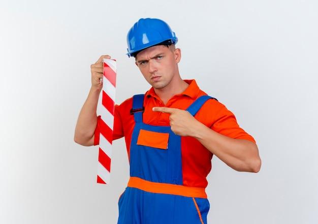 Rigoroso giovane costruttore maschio che indossa l'uniforme e la tenuta del casco di sicurezza e indica il nastro adesivo su bianco