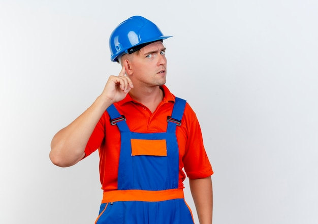 Strict young male builder wearing uniform and safety helmet putting finger on ear on white