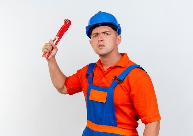 Rigoroso giovane costruttore maschio che indossa l'uniforme e casco di sicurezza che solleva la chiave a gas su bianco