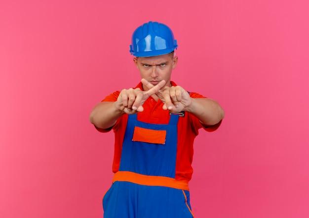 Rigoroso giovane costruttore maschio che indossa l'uniforme e il casco di sicurezza che mostra il gesto di no sul rosa