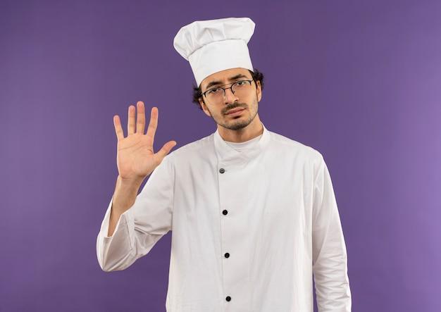 紫の停止ジェスチャーを示すシェフの制服と眼鏡を身に着けている厳格な若い男性料理人
