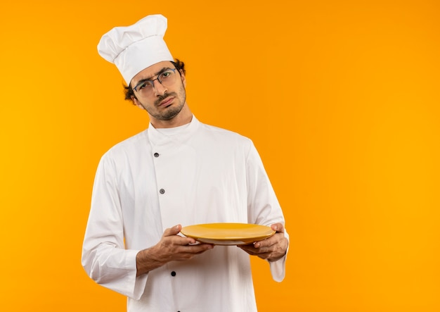Rigoroso giovane cuoco maschio che indossa l'uniforme del cuoco unico e vetri che tengono piatto isolato sulla parete gialla