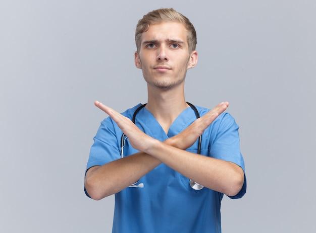 Rigoroso giovane medico maschio che indossa l'uniforme del medico con lo stetoscopio che mostra il gesto di nessun isolato sulla parete bianca