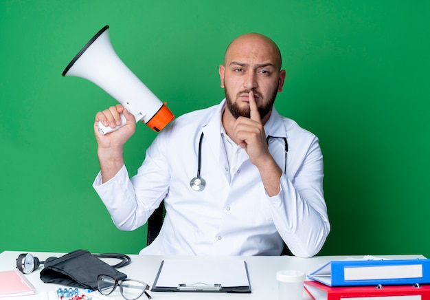 Strict young male doctor wearing medical robe and stethoscope sitting at desk