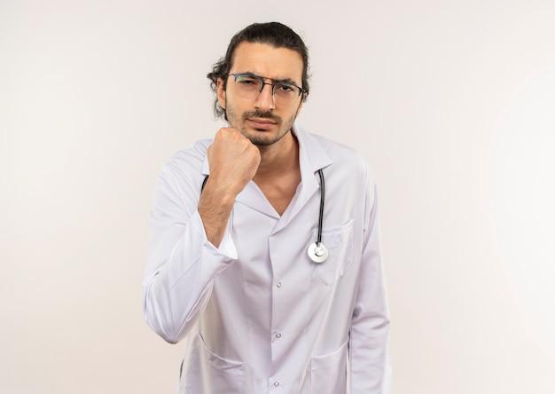 청진 기 복사 공간이 격리 된 흰 벽에 주먹을 올리는 흰 가운을 입고 광학 안경 엄격한 젊은 남성 의사