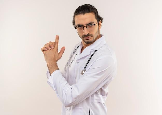복사 공간이 격리 된 흰 벽에 청진 sgowing 권총 제스처와 흰 가운을 입고 광학 안경 엄격한 젊은 남성 의사