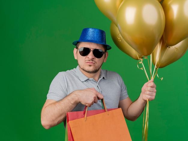 파티 모자와 녹색에 고립 된 선물 가방 풍선을 들고 안경을 착용하는 엄격한 젊은 파티 남자