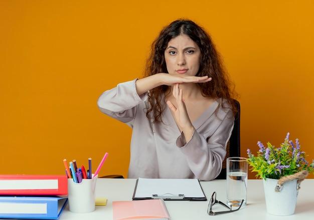 タイムアウトジェスチャーを示すオフィスツールと机に座っている厳格な若いきれいな女性のサラリーマン