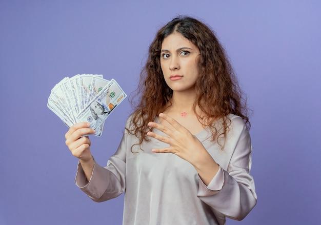 Giovane ragazza graziosa rigorosa che tiene contanti e che mostra quattro isolati sulla parete blu