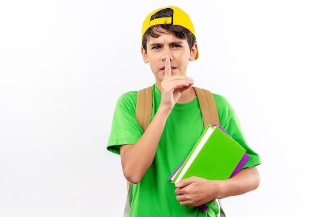 白い壁に隔離された沈黙のジェスチャーを示す本を保持しているキャップとバックパックを身に着けている厳格な少年