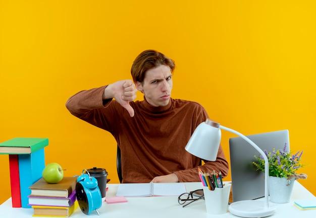 学校の道具を持って机に座っている厳格な若い学生の男の子は黄色に親指を下ろします