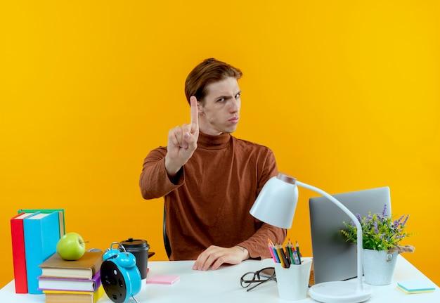 노란색 벽에 고립 된 하나를 보여주는 학교 도구로 책상에 앉아 엄격한 젊은 학생 소년