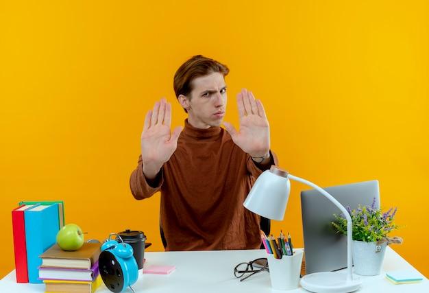 노란색 벽에 고립 된 중지 제스처를 보여주는 학교 도구로 책상에 앉아 엄격한 젊은 학생 소년