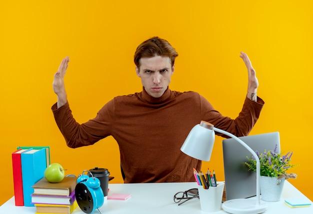 노란색 측면에 중지 제스처를 보여주는 학교 도구와 함께 책상에 앉아 엄격한 젊은 학생 소년