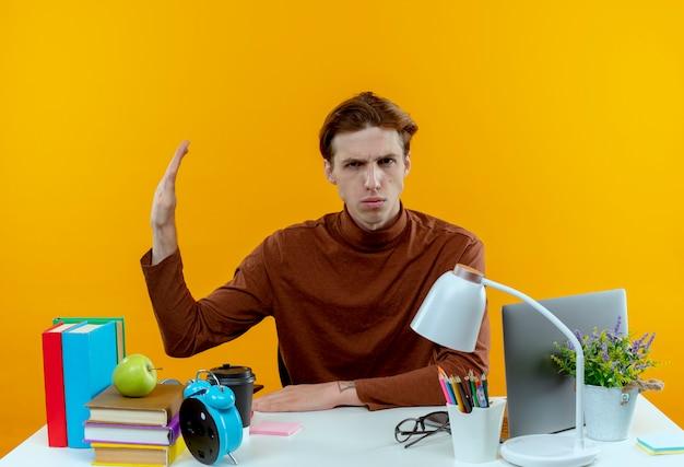 Ragazzo giovane studente rigoroso che si siede allo scrittorio con gli strumenti della scuola che mostrano il gesto di arresto fuori a lato su giallo