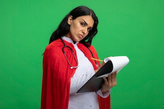 緑に分離されたクリップボードに聴診器を持って何かを書いている医療ローブを着てまっすぐ前を見てまっすぐに見ている厳格な若いスーパーヒーローの女の子