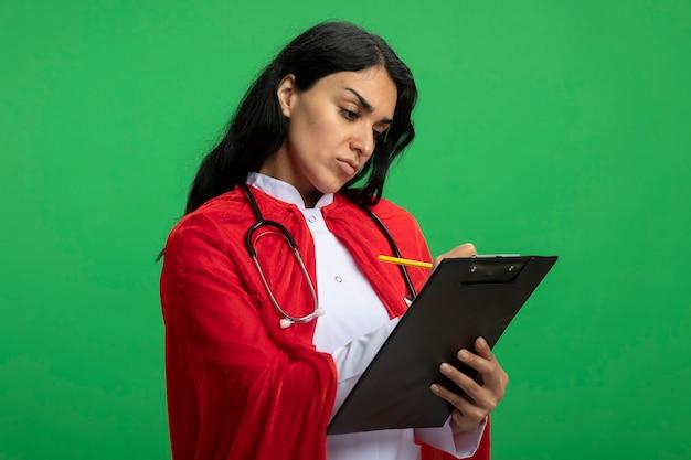 緑に分離されたクリップボードに聴診器を保持し、何かを書いている医療ローブを身に着けている厳格な若いスーパーヒーローの女の子