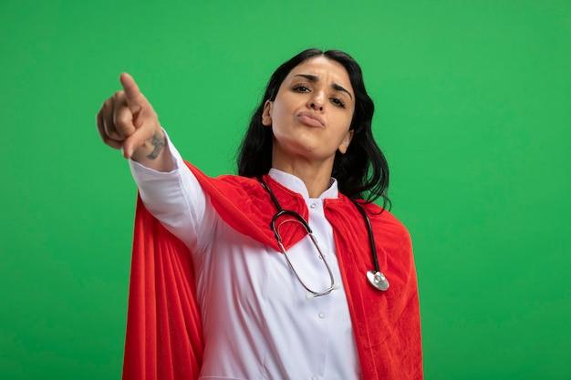 녹색에 고립 된 청진 기 의료 가운을 입고 엄격한 젊은 슈퍼 히어로 소녀