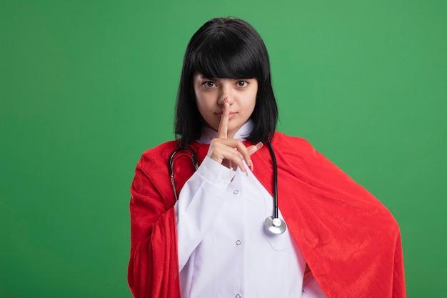 의료 가운과 녹색에 고립 된 침묵 제스처를 보여주는 망토 청진기를 착용하는 엄격한 젊은 슈퍼 히어로 소녀
