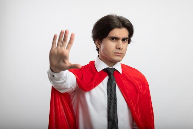 Строгий молодой супергерой, смотрящий в камеру в галстуке, показывает жест стоп, изолированный на белом