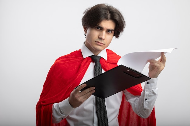 Strict young superhero guy wearing tie flipping through clipboard isolated on white background