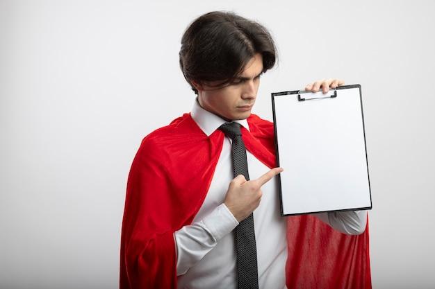 ネクタイを保持し、白い背景で隔離クリップボードを指す厳格な若いスーパーヒーローの男 無料写真
