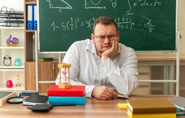 Rigoroso giovane insegnante con gli occhiali seduto alla scrivania con materiale scolastico in classe tenendo la mano sul mento guardando davanti