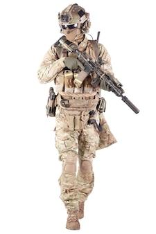 Энтузиаст страйкбола в клетчатой рубашке с военными боеприпасами, маской для лица, шлемом и радиогарнитурой, тактическими очками, камуфляжными штанами, вооруженной служебной винтовкой и студийной стрельбой из пистолета, изолированной на белом