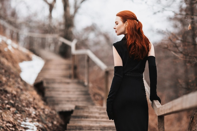 Striking girl with long red hair in black clothes. woman in black dress and long black gloves posing on a  of winter, autumn nature.