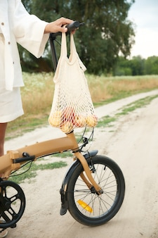 String bag with apples weighs on the handlebars of a folding bicycle next a girl in white linen suit