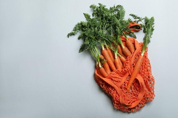 Мешок с морковью на светло-сером фоне