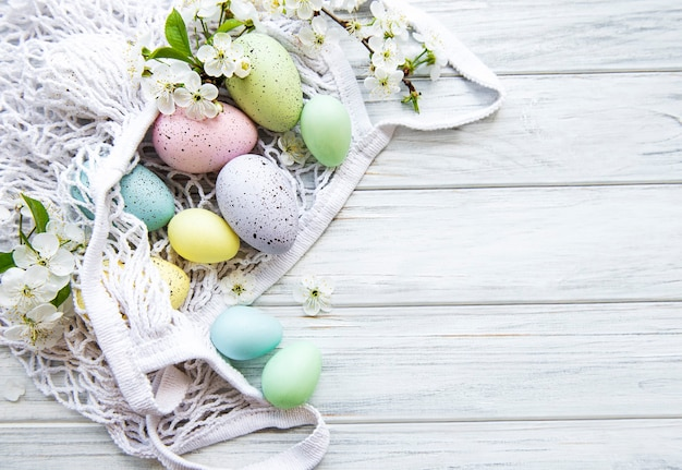 String bag with easter eggs and spring blossom in corner of a rustic wooden table