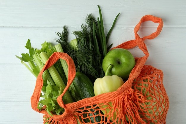 String bag with green vegetables on white wooden