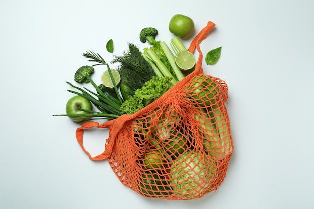 String bag with green vegetables on white