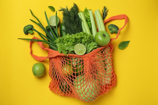 String bag with green vegetables on yellow