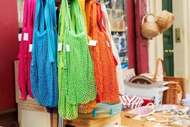 ストリングバッグ。さまざまな色のストリングバッグ、バスケットと一緒に保管してください。プラスチック、ゼロウェイストのコンセプトストアはありません。環境にやさしい環境保護ショップでリサイクル可能な再利用ショッピングバッグ。